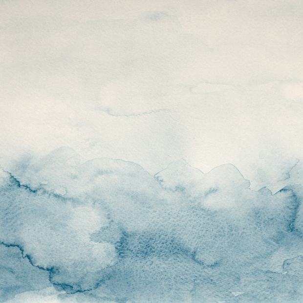 Abstract wet blue watercolor background on white watercolor paper.